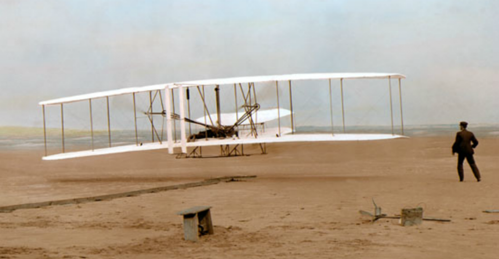 First Flight - colorized  photograph by John T. Daniels at Kitty Hawk in 1903, one of the most famous photos of all time.
